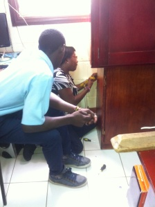 Hands on learning: a student works with the electronics teacher to re-wire an outlet